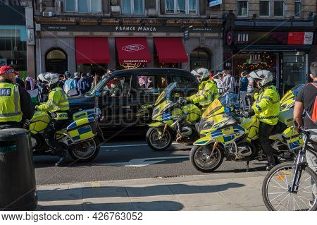 London - May 29, 2021: British Police Motorcyclists And A Black London Taxi Cab At A Freedom For Pal