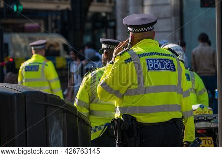 London - May 29, 2021: British Police Officer In A High Visibility Jacket Uses A Mobile Cell Phone