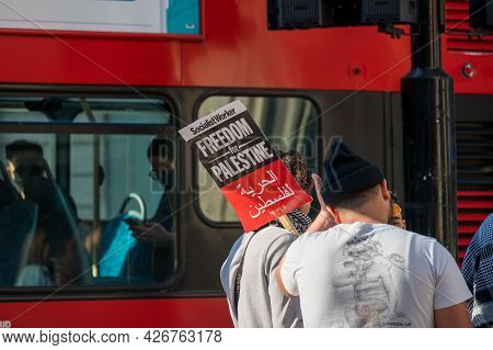 London - May 29, 2021: A Protester Holds A Placard Sign In Front Of A Red London Double Decker Bus A