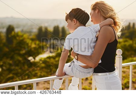 Back View Of Happy Boy Sitting On Railing And Embracing Mom While Admiring Nature Together From Obse