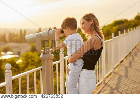 Side View Of Smiling Mom Carrying Curious Little Son Looking Through Binoculars While Standing On Ob
