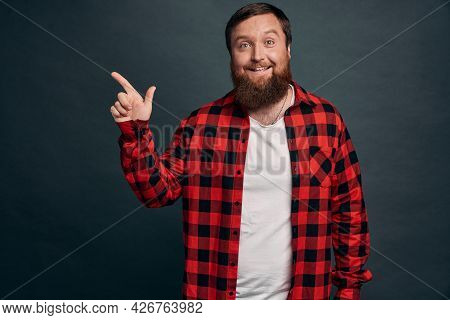 Impressed Bearded Hipster Man In Red Checkered Shirt, Pointing Left And Smiling Amused, Sharing Info