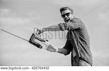 Be Careful. Macho Man Chain Saw Tool. Sexy Man Sky Background. Male Work Power Saw. He Fix Everythin