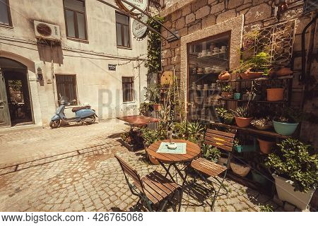 Alacati, Turkey: Small Town Restaurant In Historical Area And Vintage Scooter On Narrow Street 6 May