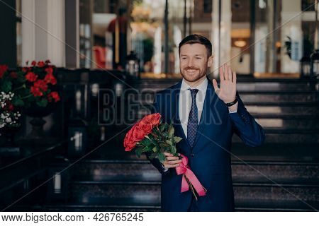 Attractive Man Waiting On Street For Date In Elegant Dark Blue Suit Holding Red Rose Flower Bouquet
