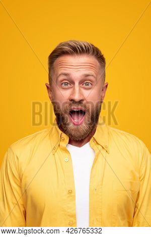 Happy Stunned Bearded Male In Casual Yellow Shirt Looking At Camera With Disbelief While Getting Unb