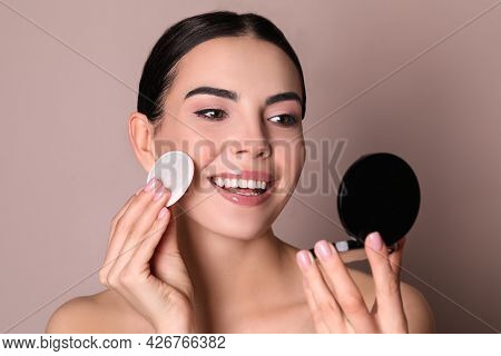 Beautiful Young Woman Applying Face Powder With Puff Applicator On Dusty Rose Background