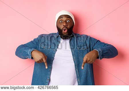 Amazed And Impressed African-american Guy Showing Advertisement, Staring At Camera Happy And Pointin