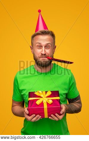 Funny Bearded Man In Party Hat Holding Wrapped Gift Box And Blowing Noisemaker During Birthday Celeb