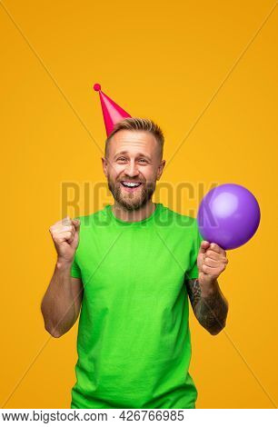 Delighted Bearded Guy With Balloon Clenching Fists And Smiling For Camera During Birthday Celebratio