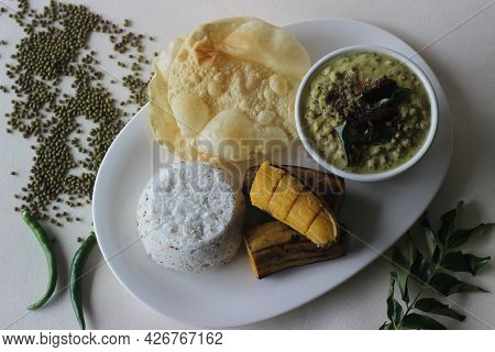 Steamed Rice Cake Served With Steamed Plantain, Green Gram Curry And Papad