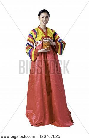 Korean Woman Is Wearing A Traditional Hanbok, She Holding A Glass Bottle Containing Kimchi, Which Is