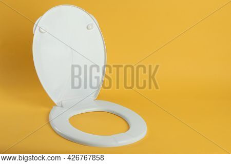 New White Plastic Toilet Seat On Yellow Background, Space For Text