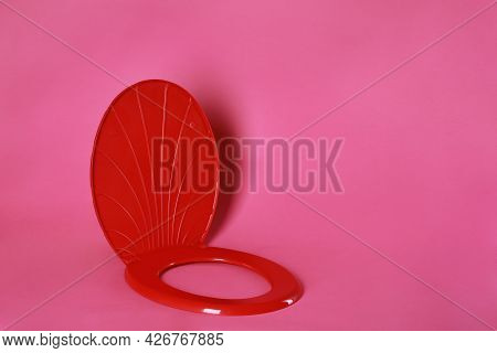 New Red Plastic Toilet Seat On Pink Background, Space For Text