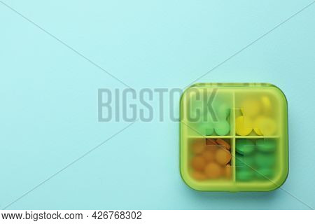 Pill Box With Medicaments On Turquoise Background, Top View. Space For Text