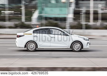 Moscow , Russia - April 2021: White Taxi Car On The Street In Motion. Side View Of Kia Rio Rides On