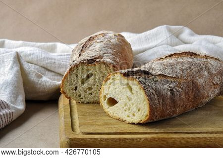 Bread Loaf, Cut Into Two Pieces, On Wooden Cutting Board. Baked Bread And Dish Towel On Craft Paper,