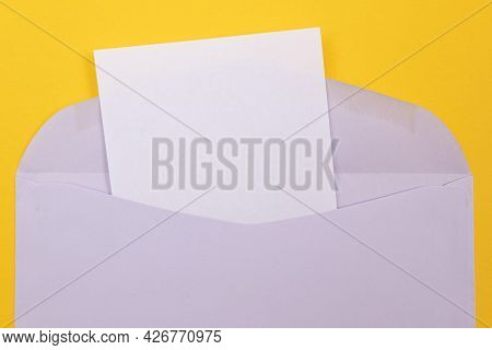 Violet Envelope With Blank White Sheet Of Paper Inside, Lying On Yellow Background - Mock Up With Co