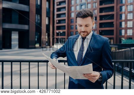 Focused Businessperson Dressed In Suit Checking Latest Newspaper For Interesting News, Standing Outs
