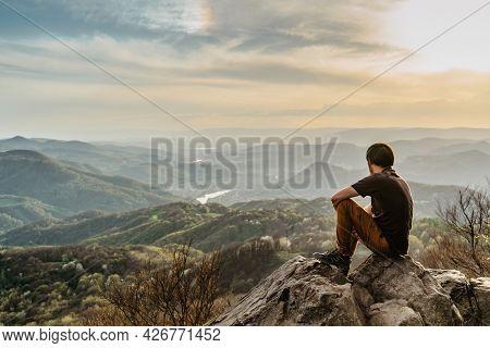 Male Traveler With Peaceful Mind Sitting On Rock Enjoying Views Of Spring Lush Valley At Sunset.hiki