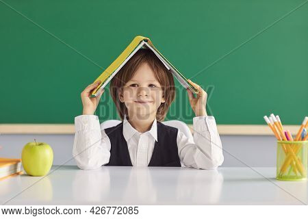 Back To School. Funny Schoolboy With A Book On His Head Smiling Looks At The Camera.