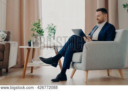 Successful Businessman In Formal Wear Sits In Comfortable Armchair Uses Modern Laptop Prepares Onlin