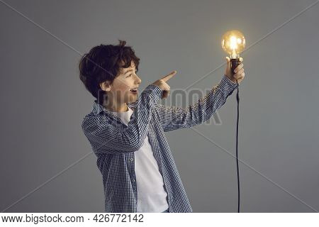 Little Happy Boy Looks With Admiration And Points His Finger At The Light Bulb In His Hand.