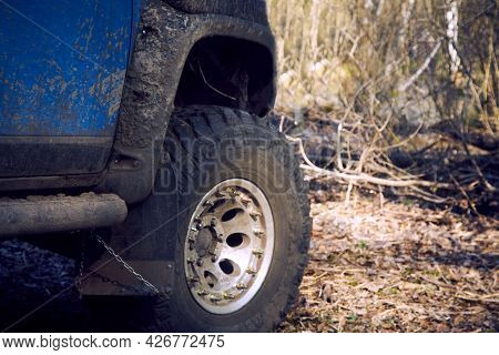 Travel Off-road On A Forest Road In A Blue 4x4 Car. The 4x4 Suv Is All Dirty