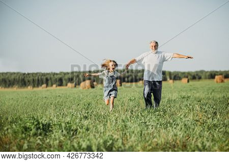 The Girl Sits On The Shoulders Of Her Grandfather While Walking In The Field. Happy Vacation Concept
