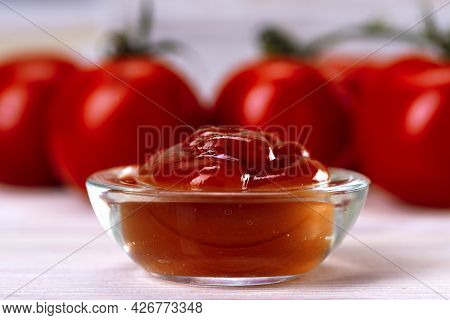 Glass Bowl Of Ketchup Or Tomato Sauce With Tomatoes On The Table Close Up.