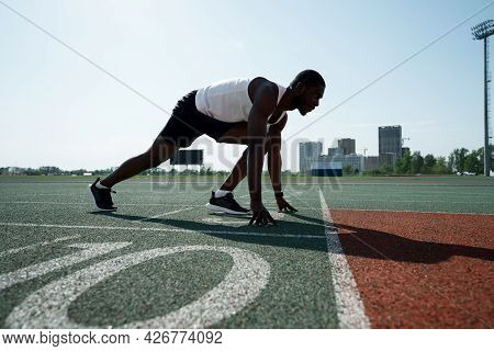 Photo From The Side. African American Athlete Run Preparing For The Race While Standing In A Pose At