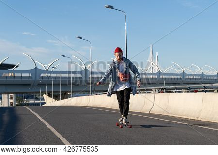 Freedom And Urban Lifestyle: Young Man Ride Longboard On City Bridge. Carefree Hipster Bearded Male