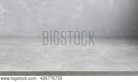 Grey table top and abstract painted  wall background texture. Front view of tabletop and wall with copy space