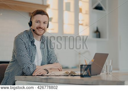 Smiling Bearded Handsome Freelancer Sitting At Home And Having Video Call While Using Headset And La