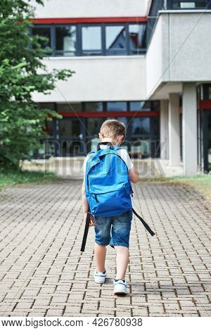 Back To School. Adorable Caucasian Boy With Blue Backpack Goes To School In First Grade After Summer