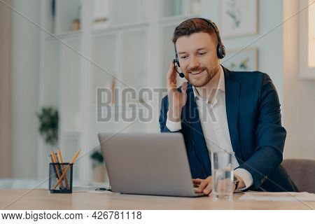Happy Successful Businessman Using Laptop And Typing On Keyboard While Sitting At The Table And Doin