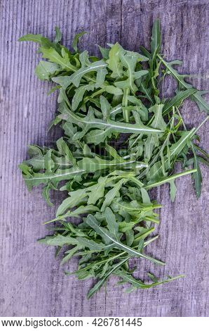 Fresh Arugula Leaves On The Wooden Table, Top View