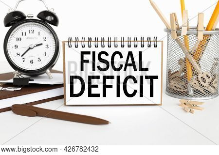 Fiscal Deficit. Text On Business Card Near Pencil Case With Pencils On White Background