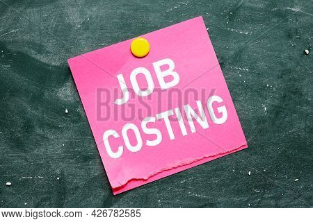 Job Costing. Text On Pink Sticker. Paper Attached To The Blackboard With Chalk. Paper Pressed By Yel