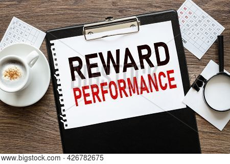 Reward Performance. Text On Wood Table, On White Paper