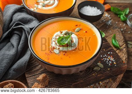 Autumn Cream Soup With Cream And Pumpkin Seeds On A Wooden Background. Side View, Close-up.
