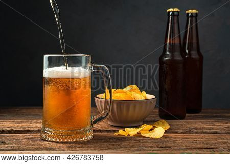 Pouring Beer Into A Glass Against The Background Of Chips And Beer Bottles. Side View, Space For Cop