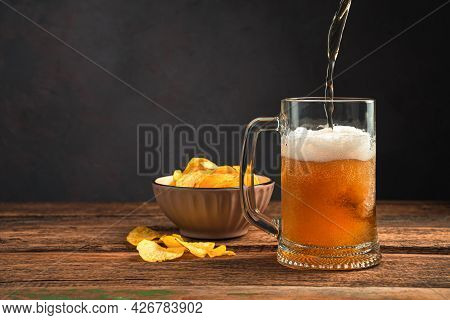 Pouring Frothy Beer Into A Mug On A Wooden Table With Chips. Oktoberfest. Side View, Space For Copyi