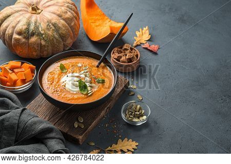 Autumn Pumpkin Soup Cream With Cream And Pumpkin Seeds On A Dark Blue Background. Side View, Space F