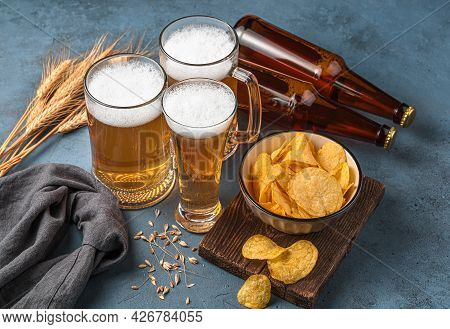 Three Beer-filled Mugs, Chips And Beer Bottles On A Dark Blue Background. Side View, Close-up. Oktob