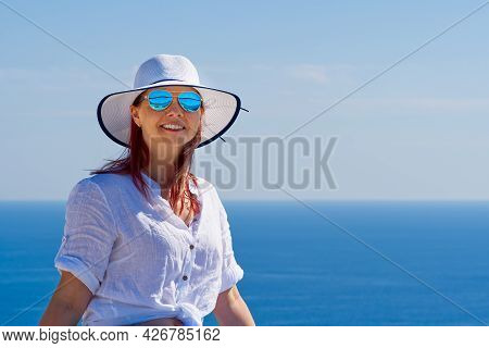 Tourist Woman In A White Straw Hat On Beautiful Blue Adriatic Sea Background. Croatia During Holiday