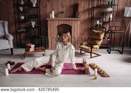 Beautiful Young Girl Sitting Relaxing On Mat With Candles In Stylish Cozy Comfort Home Interior With