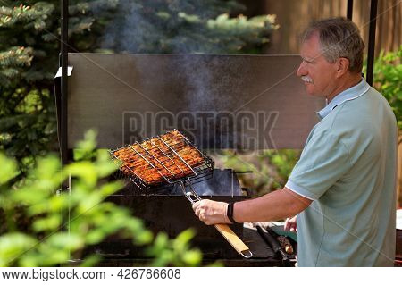 Senior Man Grilling In The Backyard Of His Country House In Sunny Summer Day. Backyard Barbecue.