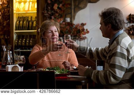 Middle Aged Couple Drinking Wine. Family Is Having Leisure Activity And Enjoying In The Restaurant