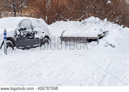 Car And Bench Among Snowdrifts After Snowstorm In Courtyard Of Town House. Winter Weather, Climate C